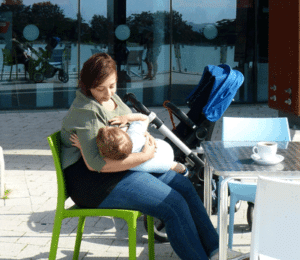 Mother breastfeeding at a cafe