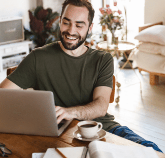 Man smiling using a laptop at home