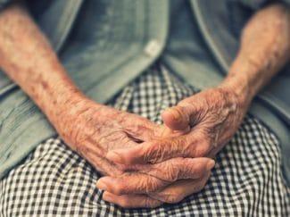 Elderly woman's hands clasped