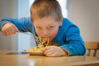 boy eating a bowl of pasta