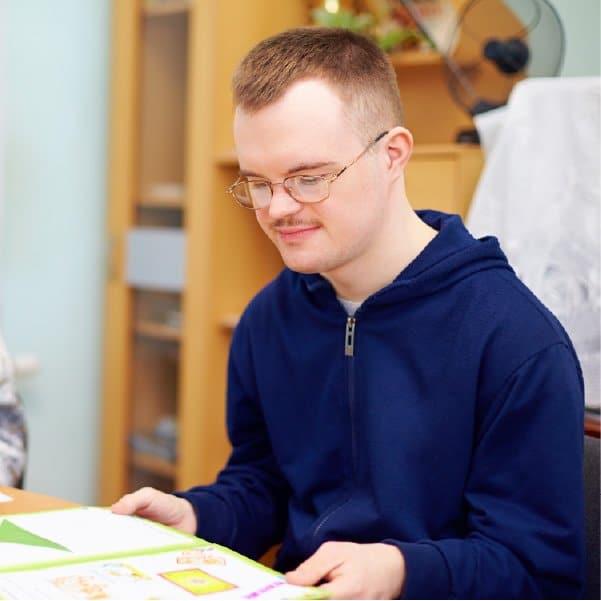 teenage boy reading a book (Devon's SEND Local Offer)