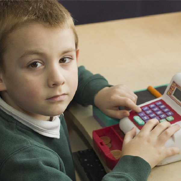 young boy playing with a till (Devon's SEND Local Offer)