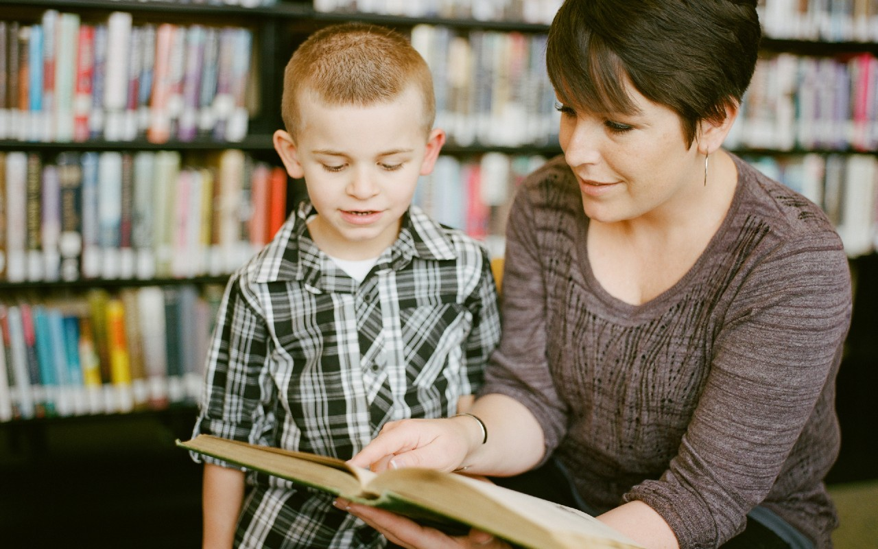 a adult reading a book with a child