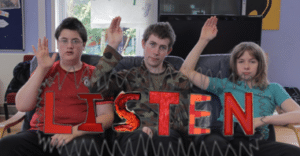 The image shows three young people, who are members of our Champions for Change group, sat down and holding their arms up with their flat palms facing forwards.  The image is accompanied by the word 'Listen' in capital red text.