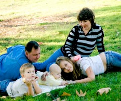Two adults an older child and two younger children sitting on grass