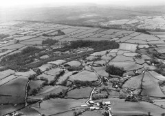 A black and white aerial photograph of the farmed landscape of Stockland reflects several phases of enclosure: prehistoric enclosures such as Stockland Little Castle (circular field centre right); irregular small medieval fields in the foreground; and distinctive large rectangular fields of nineteenth-century date on Stockland Hill.