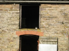 A colour photograph of a traditional farm building with a cat sitting in the hayloft opening