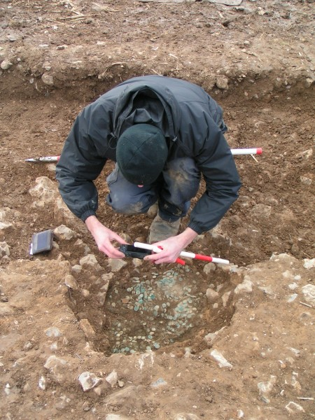 AC Archaeology recording the coin hoard in its pit. © Devon County Council