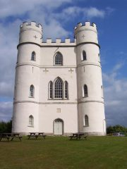 A colour photograph of a tall crenelated structure, circular turrets at each corner, rendered in white-grey with numerous arched window openings and mown grass and picnic tables in front