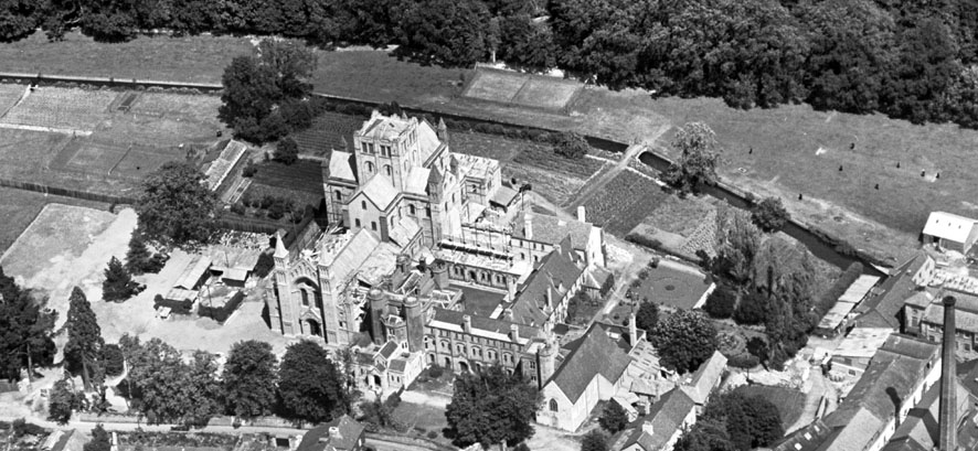 A black and white aerial photograph centred on the church, which is surrounded by monastic buildings and landscaped grounds.