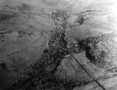 A black and white aerial photograph of a valley with sinuous earthwork ditches along the valley sides.