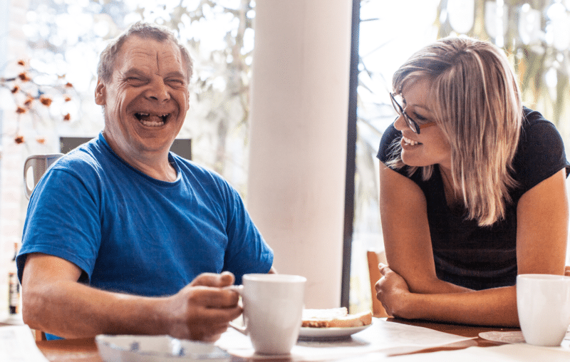 Man (who has a learning disability) laughing with his female supported living manager, sharing a smile over a mug of tea and breakfast.
