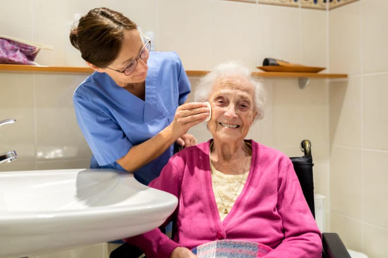 Care home worker with older woman in bathroom