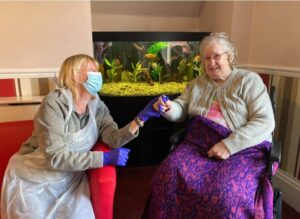 Two women in care home sitting in chairs and holding hands.