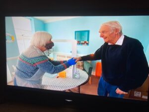 Two peopel holding hands in care home.