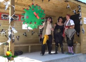 Three people dressed as pirates looking at green ball symbolising a virus.