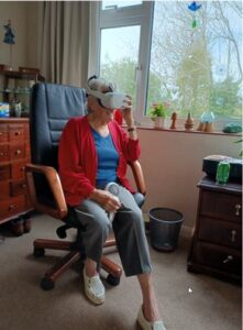 A womnan in a chair wearing a reality headset.