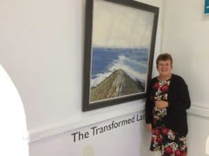 Picture of Shirley Chapman standing next to piece of art work