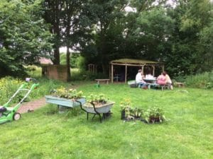 Seed of Hope participants and volunteers sat on wooden tables in the garden