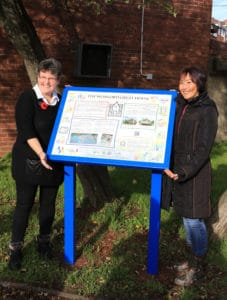 Two community members standing either side of The Wonford Great House information panel