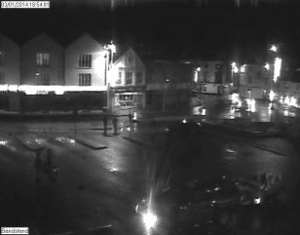 """CCTV image from 3 January 2014, Kingsbridge town square with volunteers and """"slow flood"""" and """"road closed"""" signs"""