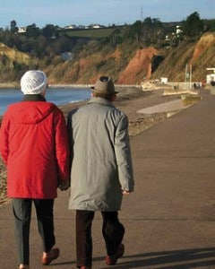 An elderly couple walking by the sea