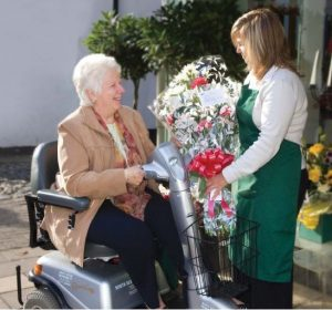 A lady on a Shopmobility scooter picking up a bouquet of flowers from a florist