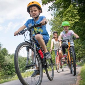 Female cycling with two young children