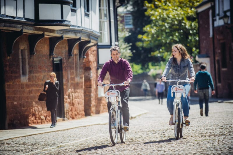 Two people cycling on electric bikes near Exeter Cathedral