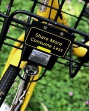 Close-up of wire basket on bicycle with label 'share more consume less'