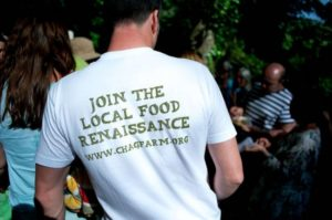 group of people gathered, man stood with back to camera wearing a white t-shirt that says join the local food renaissance www.chagfarm.org