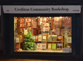 Front of crediton community bookshop with window display with a christmas tree and various books on show