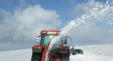 tractor in field covered in snow trying to clear snow