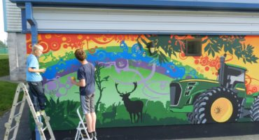 two young people stood on ladders next to green tractor mural on a colourful background