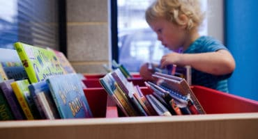 young child looking through a selection of books at library