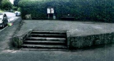 raised concrete ares with steps leading to a bench and parish noticeboard in Buckfastleigh