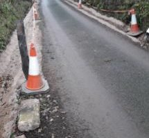 traffic cones and tape situated along roadside at Luppitt