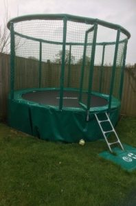 A photograph of the trampoline in the garden at Hillcrest; with a small ladder to help children climb up onto the trampoline, and netting surrounding the bouncing area to help keep users safe.
