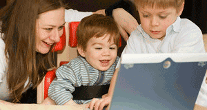 Woman and two boys looking at a laptop
