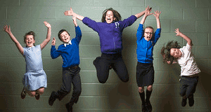 Group of 5 children jumping with their hands in the air