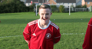 Young man with Downs Syndrome in a football kit stood on a pitch