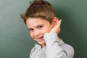 Young boy with brown hair holds his hand up to his ear as if listening
