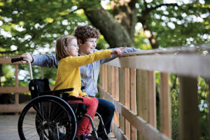 young girl in a wheelchair pointing to something outside with her male friend next to her