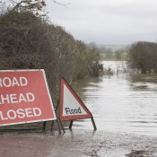 flood road closure sign next to flooded road in country lane